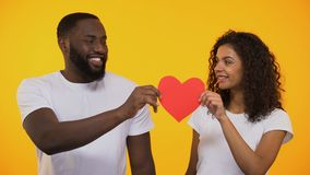 Happy multiracial couple holding red paper heart and smiling, true love and care stock footage