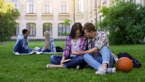 Happy multiracial couple sitting on lawn near academy and enjoying each other stock images