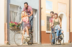 Happy multiracial friends couple having fun riding bicycle. In city old town - Friendship concept with multicultural young people on funny attitude stock image