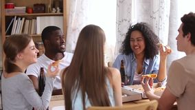 Happy multiracial friends eating pizza drinking beer talking in pizzeria. Happy multiracial friends eating pizza drinking beer sharing table in pizzeria pub stock video footage