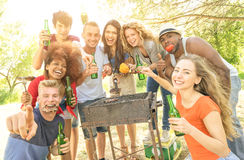 Happy multiracial friends having fun at barbecue garden party. Happy multiracial friends having fun at picnic barbecue garden party - Friendship concept with Stock Photos