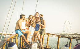 Happy multiracial friends having fun on sailing party boat Stock Images