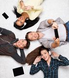 Happy multiracial friends relaxing with gadgets. Happy multiracial friends relaxing on a carpet with gadgets Royalty Free Stock Images