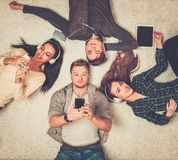 Happy multiracial friends relaxing with gadgets. Happy multiracial friends relaxing on a carpet with gadgets Stock Images