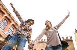 Happy multiracial girlfriends having genuine fun walking in city center - Friendship concept with girls at old town tour. Happy multiracial girlfriends having royalty free stock photos