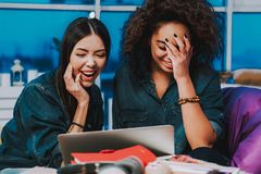 Happy multiracial girls watching at laptop indoors stock photo