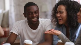 Happy multiracial young people friends talking laughing at group meeting
