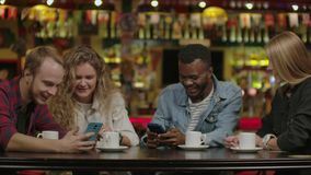 Happy multiracial young people friends talking laughing at group meeting sharing cafe table, diverse students drinking. Coffee having fun together enjoy multi stock video