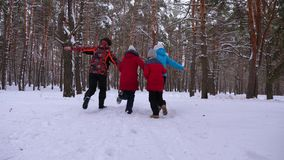 Happy mum and dad run with children through the winter forest. parents play with children in a snowy park in winter. Happy family walks in Christmas forest royalty free stock images