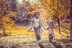 Happy mum and the daughter play autumn park. Beautiful mum and daughter happily spend time in autumn garden royalty free stock images