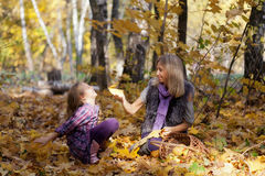 Happy mum and the daughter play autumn park Royalty Free Stock Photography