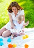 Happy mum and her Child playing in Park together Stock Photo