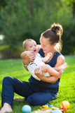 Happy mum and her child playing in park together Royalty Free Stock Photography