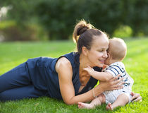 Happy mum and her child playing in park together Stock Image