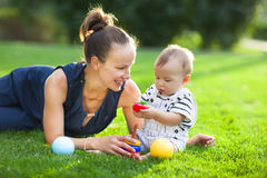 Happy mum and her child playing in park together Royalty Free Stock Image