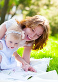 Happy mum and her Child reading in park together Royalty Free Stock Photos