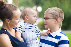 Happy mum and her children playing in park together Stock Photo