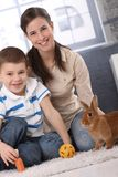 Happy mum and little son playing with rabbit. Happy mum and little son playing with domestic rabbit at home, carrot and ball Royalty Free Stock Images