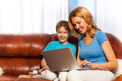 Happy mum and son with laptop on the sofa Stock Photos