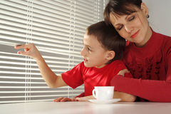Happy Mummy Hugs Her Son Sitting At A Table Royalty Free Stock Photography