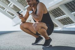 Happy muscular fit sport model sprinter resting after his workout and using mobile phone for check his results. Happy muscular fit sport model sprinter resting royalty free stock photo