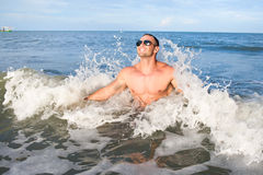 Happy muscular male enjoying the sea Stock Images