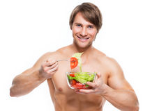 Happy muscular man eating a salad. Stock Photos