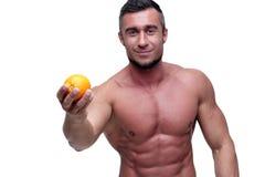 Happy muscular man holding orange. Over white background Stock Image