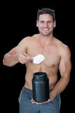 Happy muscular man scooping up protein powder Royalty Free Stock Image