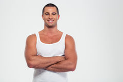 Happy muscular man standing with arms folded Royalty Free Stock Images