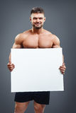 Happy muscular shirtless man showing and displaying placard Royalty Free Stock Images