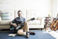 Happy music composer in home studio. Smiling male music composer sitting on floor with a book and guitar stock image