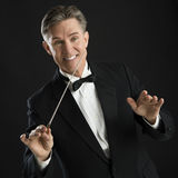 Happy Music Conductor Gesturing While Directing With His Baton. Happy mature male music conductor gesturing while directing with his baton against black Royalty Free Stock Photography