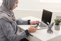 Arabic businesswoman in hijab working at office. Happy muslim businesswoman in hijab at office workplace. Smiling Arabic woman working on laptop and messaging on Royalty Free Stock Images