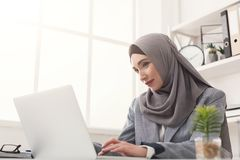 Arabic businesswoman in hijab working at office. Happy muslim businesswoman in hijab at office workplace. Smiling Arabic woman working on laptop on startup Royalty Free Stock Photography