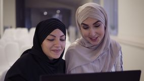 Happy muslim businesswomen in hijab at office workplace or conference hall. Two smiling arabic woman working on laptop stock video