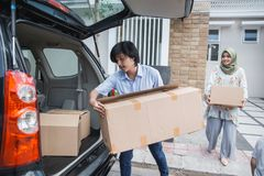 Couple carry cardboard box moving to new house. Happy muslim couple carry cardboard box moving to new house Royalty Free Stock Photo