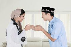 Happy Muslim couple forgiving each other at home. Happy Muslim couple forgiving each other during Eid Mubarak celebration at home royalty free stock photography