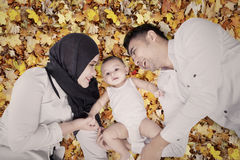 Happy muslim family on autumn leaves Royalty Free Stock Photo