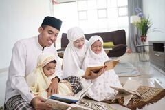 happy muslim family with children reading quran and pray together