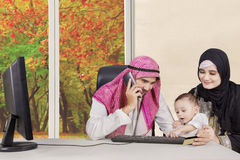 Happy muslim family at the living room. Image of muslim parent with little baby shopping online together at home in autumn season royalty free stock photo
