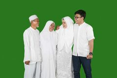 Happy muslim family portrait with parents, son and daughter laughing together