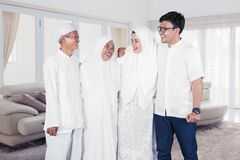 Happy muslim family portrait with parents, son and daughter laughing together in living room