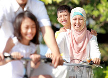 Happy muslim family riding bikes Stock Image