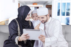 Happy muslim family use tablet on the sofa royalty free stock image