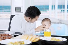 Happy muslim father feeding his baby. Portrait of happy muslim father feeding his cute baby with hand on the table at home Stock Photos