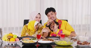 Muslim father having dinner with his family. Happy muslim father having dinner with his family and giving date palm fruits to his children. Shot in 4k resolution stock video footage