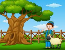 Happy muslim kid with a sheep beside a tree inside the fence Royalty Free Stock Photo