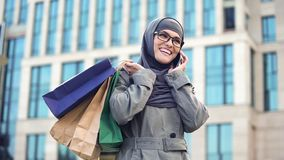 Happy Muslim lady chatting on phone outdoors shopping mall, black Friday sale. Stock photo royalty free stock photography