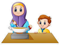 Happy Muslim mom cooking with her son Royalty Free Stock Photo